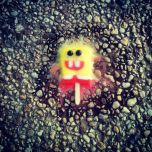 A melted Spongebob Squarepants popsicle on the ground.