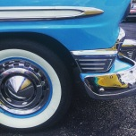 A close up view of the front bottom section of a 1950's blue car with chrome details.