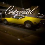 "The reflection of Elvis' yellow Pantera through the side of a Continental car, with the word, ""Continental"" above the Pantera's reflected image."