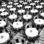 Black and white pattern of empty circular tables and chairs on a geometric patterned floor.