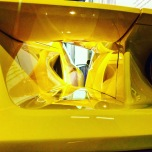 Seeing through the shapes of the side of a yellow Ford GT.
