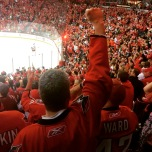 A fan with his fist raised upwards, inside a crowded stadium of Washington Capitals fans.