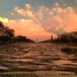 Sunset on The National Mall which is muddy with reflecting puddles. The Capitol stands in the background.