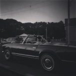 A dark black and white photo of a couple in an older Mercedes convertible while driving.