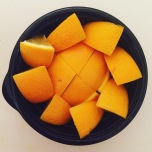 A view from above of orange slices arranged in a circular pattern in a black bowl.