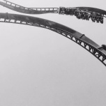 Black and white section of a roller coaster twisting above.