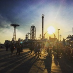A busy flow up people walking beside the Coney Island amusement park at sunset.
