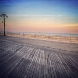 A pastel sunset against an empty boardwalk at Coney Island, NY.