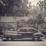 A Sepia scene of an antique car parked on a street.