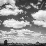 Black and white view of the Baltimore skyline in the distane with a scattered cloudy sky above.