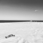 Black and white beach scene with plastic flip flops in the foreground.