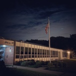 A still night time scene of an older elementary school.